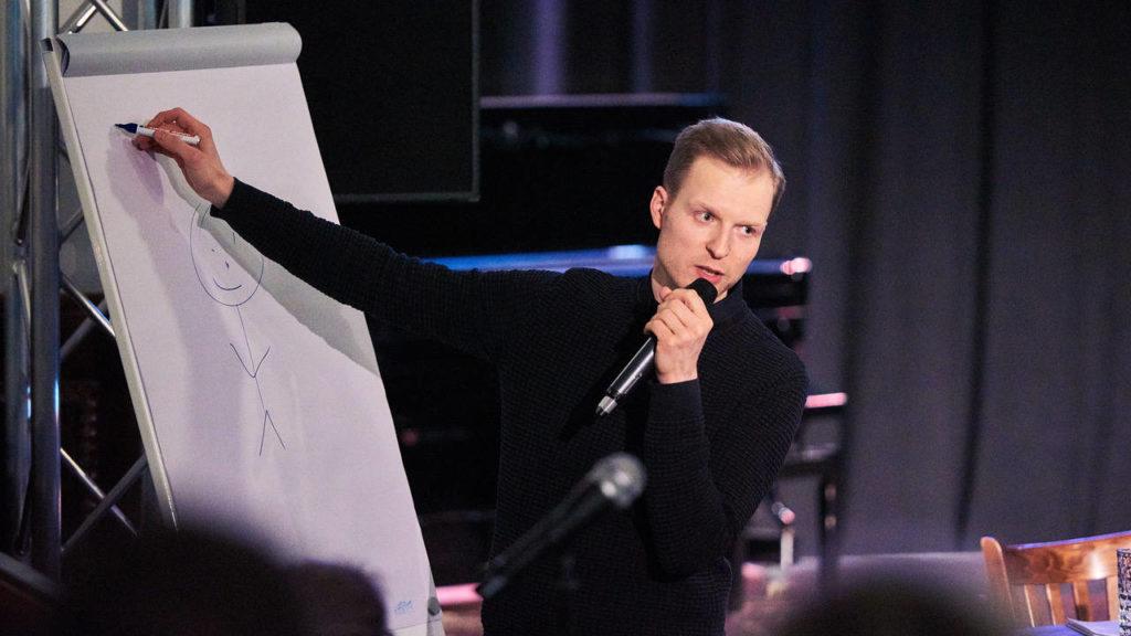Marcell Heinrich erklärt und zeichnet auf einem Flip Chart.