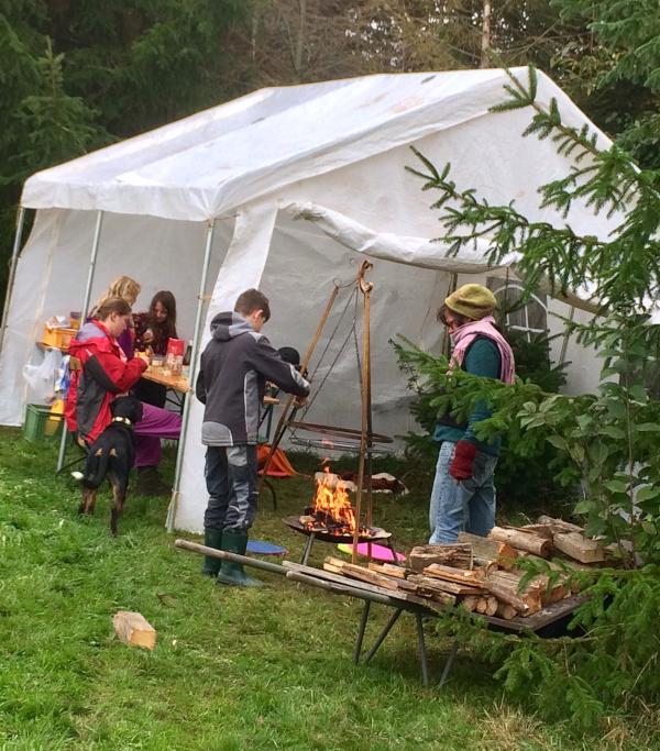 Kinder bereiten mit Erwachsenen Essen am Feuer zu