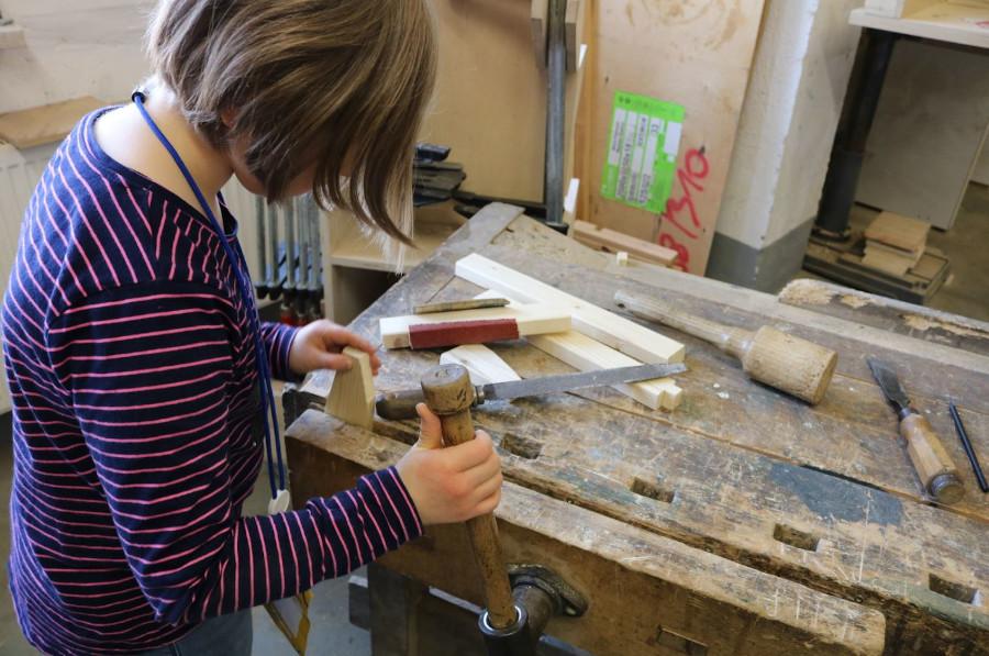 Ein Mädchen arbeitet in der Wolzwerkstatt
