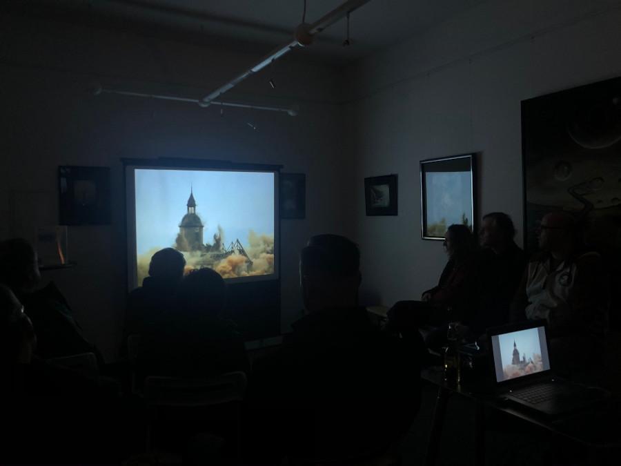 Besucher schauen einen Film bei der Kunstausstellung