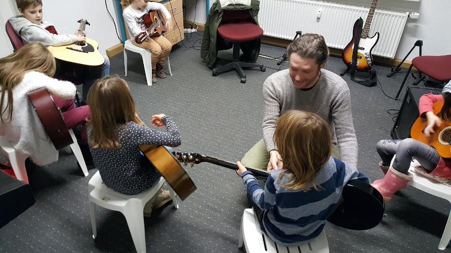 Kinder lernen mit einem Lehrer Musikinstrumente kennen