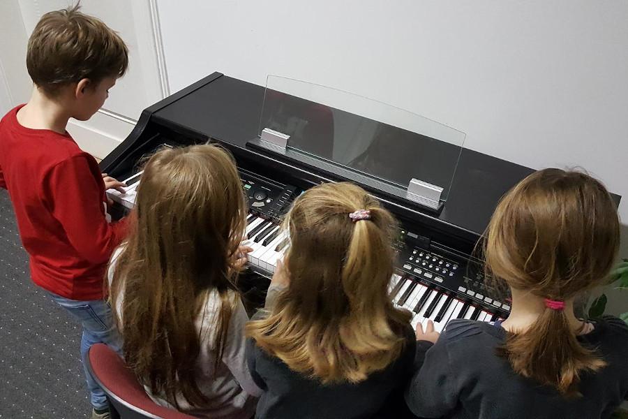 Kinder probieren sich gemeinsam am Keyboard