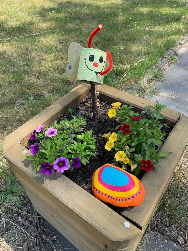 Ein Hochbeet mit bunter selbstgestalteter Gartendekoration