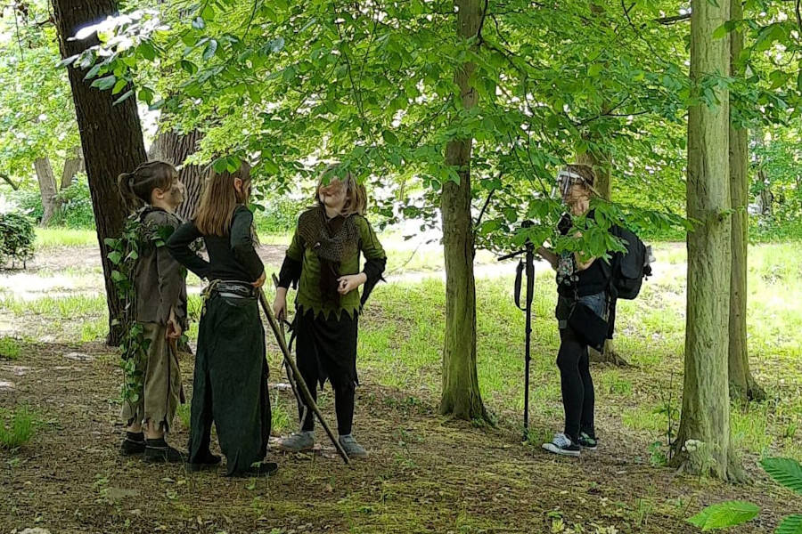 Kinder proben unter Bäumen kostümiert eine Szene