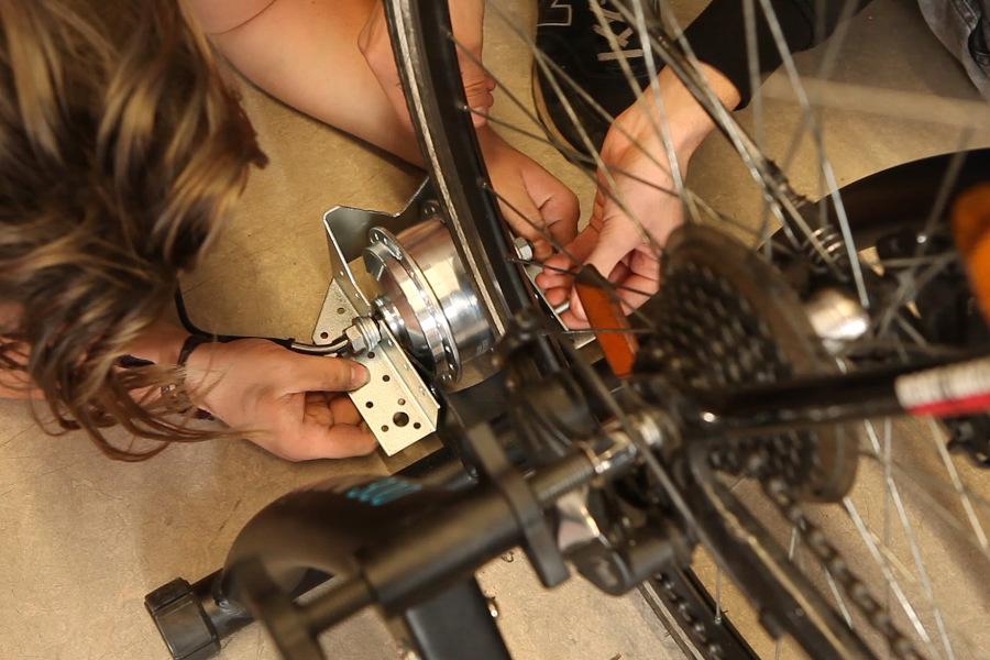 Die Jugendlichen befestigen den Generator am Fahrradreifen