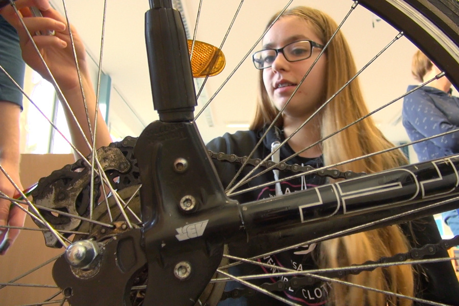 Eine Schülerin der Oberschule werkelt am Hinterrad