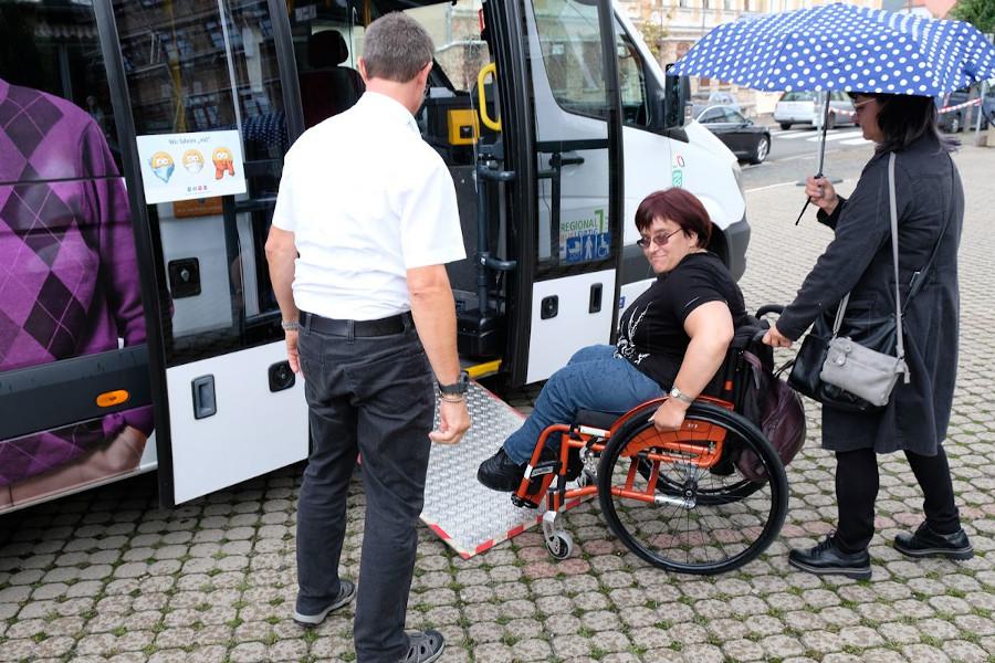 Eine Rollstuhlfahrerin fähr auf der Rampe in den Bus